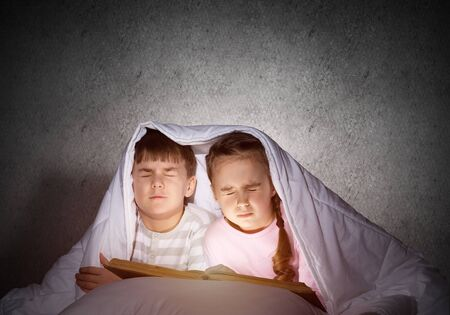 Children with flashlight lying in bed. Little girl and boy with closed eyes hiding under blanket together. Covered kids afraid of dark at night on background of grey wall. Night terrors of child