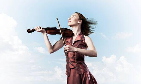 Junges attraktives Mädchen, das Geige über blauem Himmel und Wolke spielt