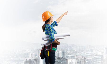 Ingeniera en casco de pie con planos técnicos y apuntando hacia arriba. Vista lateral del arquitecto de la mujer en camisa azul a cuadros que inspecciona la construcción. Gestión y auditoría de proyectos de edificación.