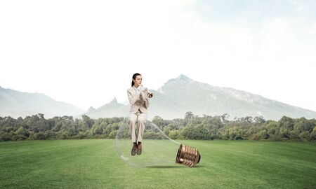 Business woman sitting on big light bulb and playing trumpet brass. Young lady in white business suit and gloves with music instrument on green field. Musician practicing and performing outdoors