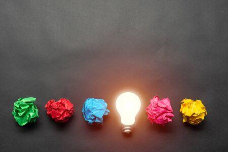 Bombilla y bolas de papel de colores arrugadas sobre fondo negro. Solución exitosa del problema. Generación de ideas y lluvia de ideas. Idea de genio entre metáfora de ideas fallidas. Motivación empresarial Foto de archivo