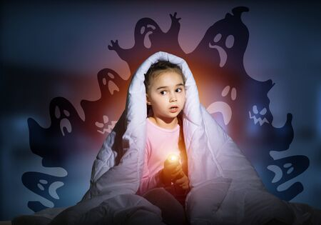 Scared girl with flashlight hiding under blanket from imaginary phantoms. Frightened kid sitting in bed on night sky background. Night terrors of child. Girl in pajamas and boo ghosts silhouettes Banco de Imagens