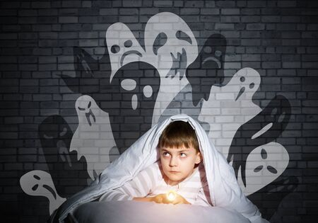 Frightened child with flashlight hiding under blanket. Halloween scary ghostly monsters on wall. Scared kid in pajamas lying in his bed at home. Fear of the dark. Little boy can not sleep at night.
