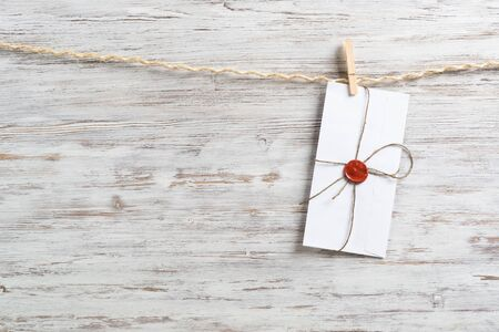 White classic envelope hanging on twine rope with clothespins. Vintage declaration of love on wooden painted background. Retro letter envelope with sealing wax stamp. Romantic wedding invitation. Archivio Fotografico