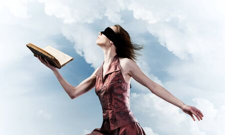Young woman in red long dress and blindfold with book in hand Stockfoto