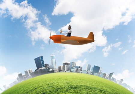 Screaming businessman in leather helmet flying in propeller plane. Emotional aviator driving small airplane above cityscape. Rounded city skyline with green grass, blue sky and modern skyscrapers