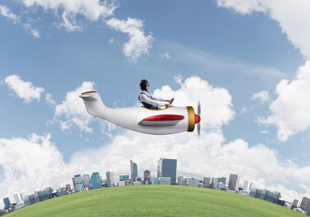 Aviator driving propeller plane above business center. Pilot in leather helmet sitting in airplane and holding steering wheel. Rounded of city skyline with high skyscrapers and office buildings.