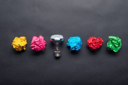 Lightbulb and crumpled colorful paper balls on black background. Successful solution of problem. Idea generation and brainstorming. Genius idea among failing ideas metaphor. Business motivation