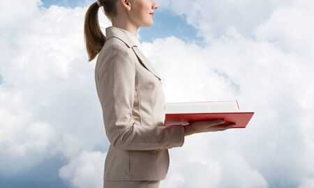 Business woman holding open notebook on background of sky. Professional consulting and consultation. Closeup open book with red cover in female hands. Side view young woman in white suit. Stock Photo