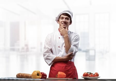 Young smiling chef standing near cooking table with fresh vegetables. Pleased chef in white hat and red apron in light kitchen interior. Cooking classes advertising. Restaurant food preparation