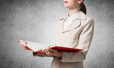 Corporate employee holding open notebook on background of grey wall. Business paperwork and accounting. Closeup open book with red cover in female hands. Elegant young woman in business suit.