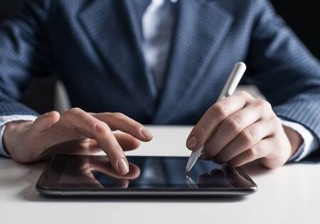 Man in business suit using digital tablet computer. Close-up of male hand holding pen and tablet device. Business man at workplace in office. Mobile smart device in business occupation.
