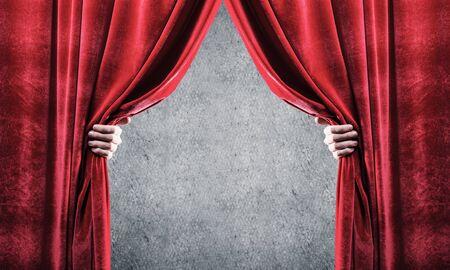 Chiuda in su della tenda di velluto rosso aperta a mano d'affari. Inserisci il tuo testo Archivio Fotografico