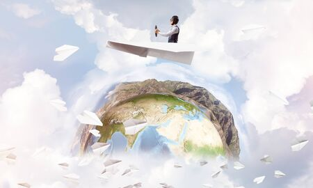 Pilot in leather helmet driving paper plane on background of blue cloudy sky. Funny man flying in small paper airplane. Spherical view of earth planet with lands, ocean and mountains.