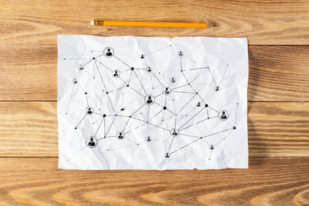 Social network structure pencil hand drawn with social connection lines. Company employees organization sketch on wooden surface. Top view of workplace with white paper and pencil lying on wooden desk Stock Photo