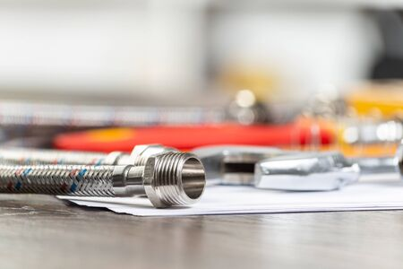 Water braided metal hose with connecting internal screw. Close up flexible hydraulic system. Plumbing pipeline laying on office table. Water hosepipe planning and installation project.