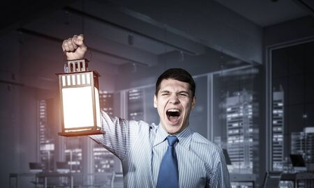 Screaming businessman holding glowing lantern on background office interior. Front view of emotional man in shirt and tie looking for something in dark. Scared business person walking with lantern