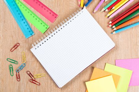 Back to school concept with blank notepad stickers and pencil on wooden surface