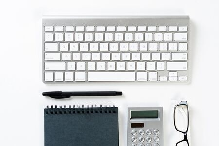 Still life of accountant workspace with office accessories. Flat lay white desk with computer keyboard, calculator and notepad. Accounting and banking services. Finance and investment concept.