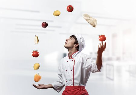 Young male chef juggles with food ingredients. Handsome chef in white hat and red apron in light kitchen interior. Professional cooking classes advertising. Food retail campaign announcement.
