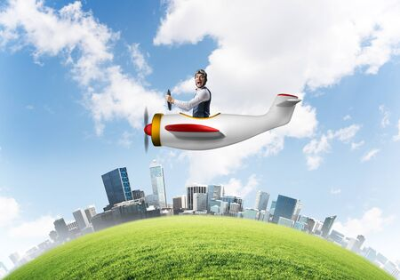 Screaming businessman in leather helmet flying in propeller plane. Emotional aviator driving small airplane above cityscape. Rounded city skyline with green grass, blue sky and modern skyscrapers Reklamní fotografie