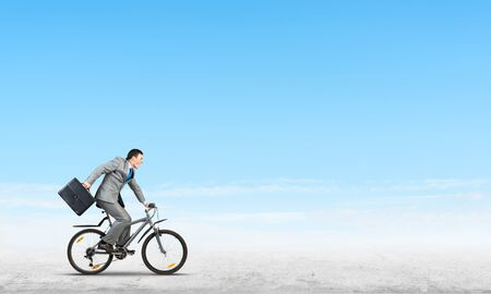 Man wearing business suit riding bicycle outdoor. Cyclist with suitcase on background of blue sky. Time management and business activity. Businessman hurrying to work. Business competition and career