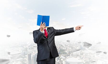 Businessman covered his face with organizer and finger pointing side. Man in business suit and tie standing on cityscape background with flying paper planes. Education and professional knowledges.