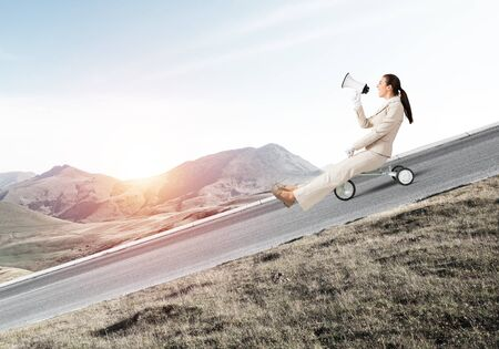 Woman shouting into megaphone and riding downhill on road. Young employee in white business suit going down on small bike outdoor. Fast business startup. Advertising and promotion concep