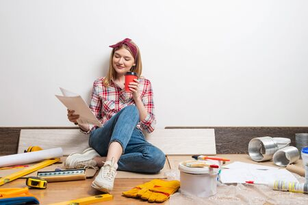 Interior designer studying renovation project. Smiling pretty girl sitting on floor with paper blueprint. Home remodeling and house interior redesign. Construction tools and materials for building. Stok Fotoğraf