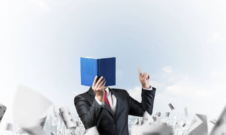 Businessman covered his face with organizer and finger pointing up. Man in business suit and tie standing on cityscape background with falling paper documents. Education and professional knowledges. Imagens