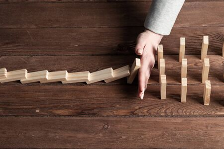Businesswoman protecting dominoes from falling on wooden desk. Business assistance and leadership in crisis. Operative business solution and stabilization of situation. Professional risk management