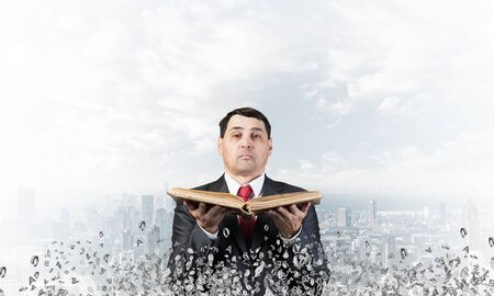 Senior businessman holding old open book. Man in business suit and tie standing on cityscape background with flying around various letters. Manager holding handbook. Reference information concept
