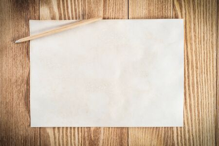Sheet of paper lying on wooden table. Blank white a4 format paper with pencil. Space for writing and notification. Textured natural wooden background. Vintage copy space for creative design.