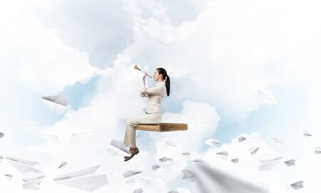 Young woman playing trumpet and flying on book in blue sky. Girl in white business suit posing with music brass instrument. Imagination and inspiration. Business education concept with paper planes.