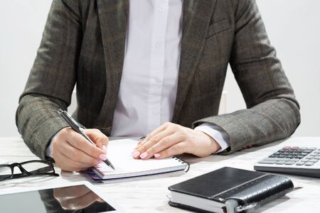 Close up woman hand holding pen. Businesswoman writing in notepad. Female accountant working at desk. Corporate woman in suit at her workplace in office. Business person doing notes on paper.