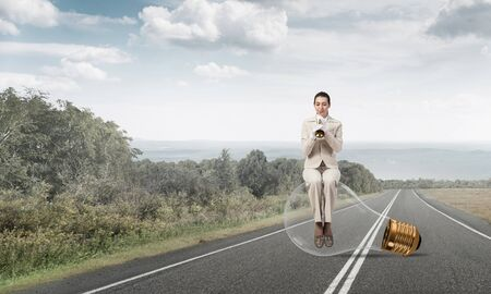 Beautiful woman playing trumpet brass on asphalt road. Young businesslady in white business suit and gloves sitting on big light bulb with music instrument. Musician practicing and performing outdoor
