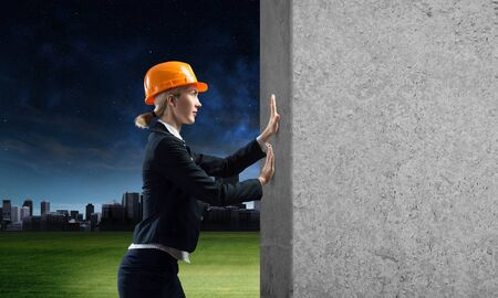 Beautiful woman architect pushing concrete wall. Young specialist in safety helmet on night city background. Sale building material and services. Grey concrete wall as banner with copy space.