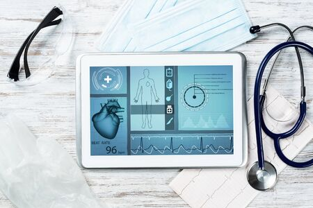 Medical diagnostics in hospital. Tablet computer with medical app interface on screen. Doctor workplace with stethoscope and cardiogram on wooden desk. Digital technology in cardiology clinic.