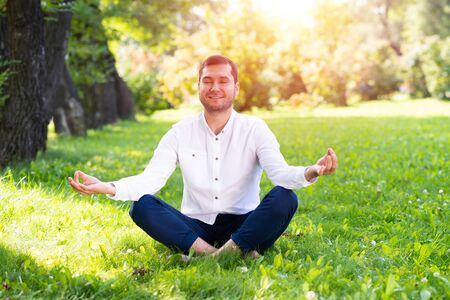 Young man meditates in lotus pose on green grass. Handsome man in casual wear practicing of yoga with closed eyes. Training and meditation outdoor at summer day. Healthy lifestyle and relaxation.