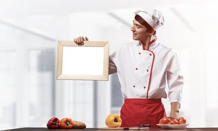 Young male chef standing near cooking table and holding blank white board. Handsome chef in white and red uniform in light kitchen interior. Cooking classes advertising. Professional catering service