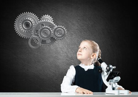 Little girl scientist with microscope on chalkboard background with gears mechanism. Research and discovery concept. Elementary science class in modern school. Schoolgirl in schoolwear sitting at desk