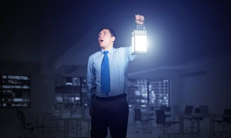 Businessman with glowing lantern looks suspicious on background office interior. Young corporate employee in shirt and tie looking for something at night. Portrait of distrustful man lost in dark.