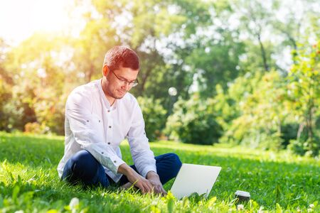 Young businessman sitting on green grass and using laptop computer. Handsome man working with computer in park at sunny summer day. Outdoors nature journey and relaxation. Freelance work concept.
