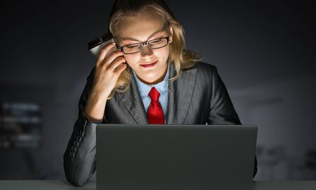 Portrait of concentrated businesswoman in glasses sitting at office desk and working at laptop. Financial consultant in business suit and tie busy at work in evening. Working in office late at night. Stockfoto