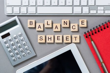 Balance sheet concept with letters on wooden cubes. Still life of office workplace with supplies. Flat lay grey surface with tablet computer and calculator. Budget planning, audit and accounting.