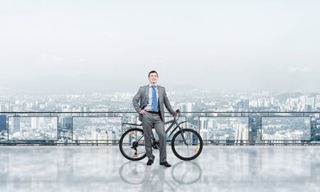 Happy man wearing business suit standing on balcony with bike. Businessman with bicycle on background of sky above megalopolis. Smiling cyclist holding bicycle on terrace with modern downtown view.