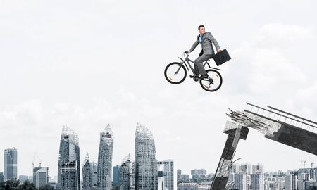 Man on bike jumping from broken bridge. Businessman looking back on bike and hurry to work. Employee in business suit with suitcase on cycle flying in air. Cyclist on background cityscape and blue sky