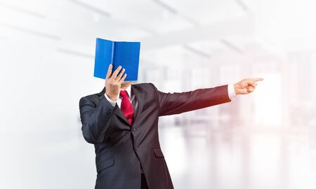 Businessman covered his face with book and finger pointing side. Portrait of man in business suit standing in blurred office interior. Education and professional knowledges. Reference information.