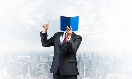 Businessman covered his face with organizer and finger pointing up. Man in business suit and tie standing on cityscape background. Education and professional knowledges. Direction and instruction.