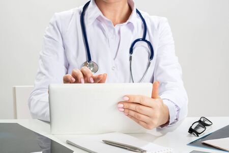 Close up female doctor hands using tablet computer. Family physician in white coat with stethoscope sitting at desk. Professional medical diagnosis and treatment in clinic. Medical online application Stok Fotoğraf